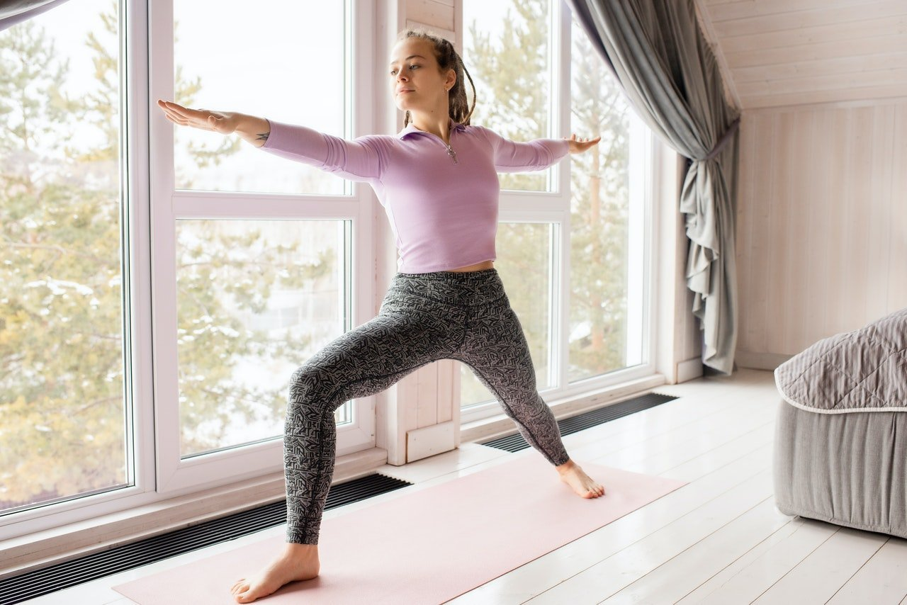 Young woman in bedroom holding yoga post during quarantine