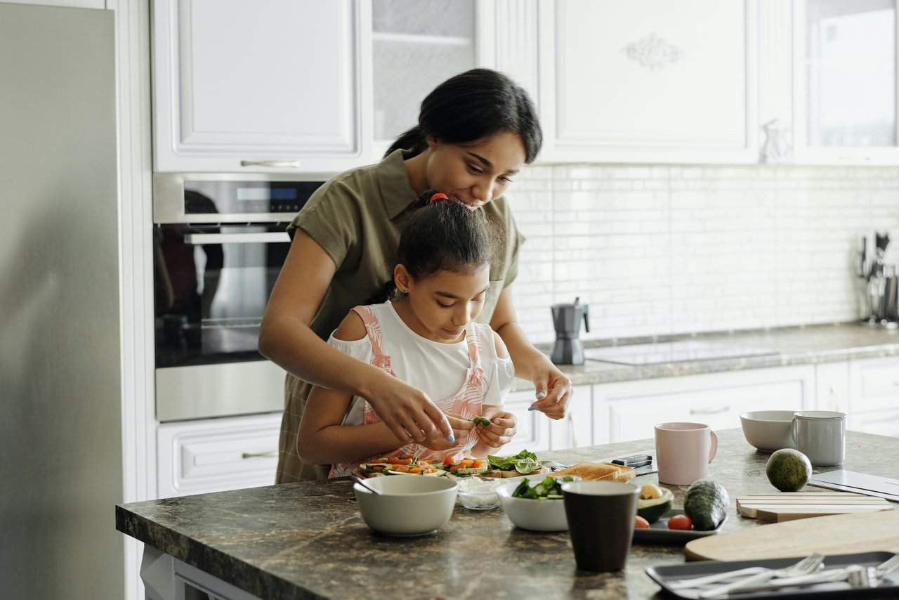 Mother and daughter cooking gluten-free meal.