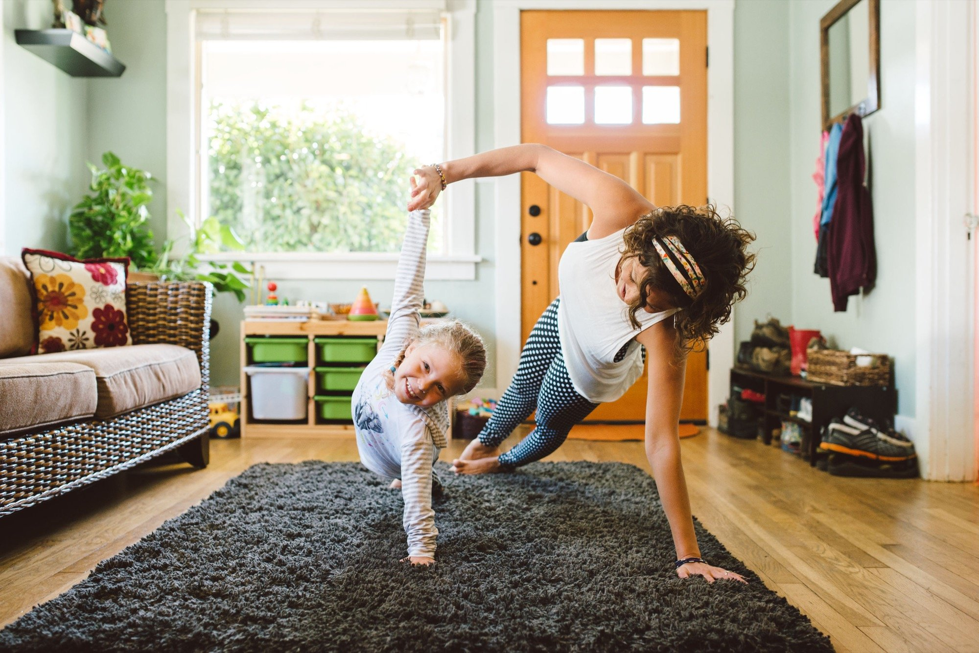Young Girl Does Yoga In Living Room With Her Mom.