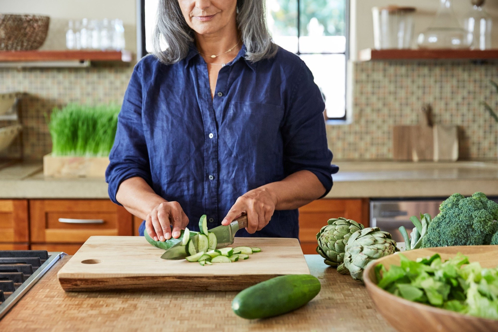 Mature woman cutting vegetables in clean kitchen to prevent foodborne illness.
