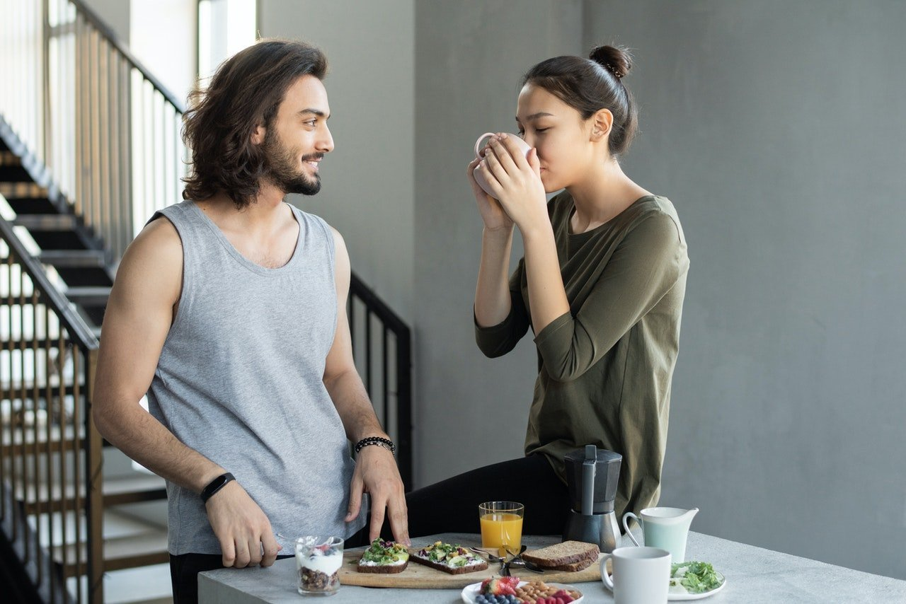 Young couple in kitchen eating breakfast that contains healthy fats.
