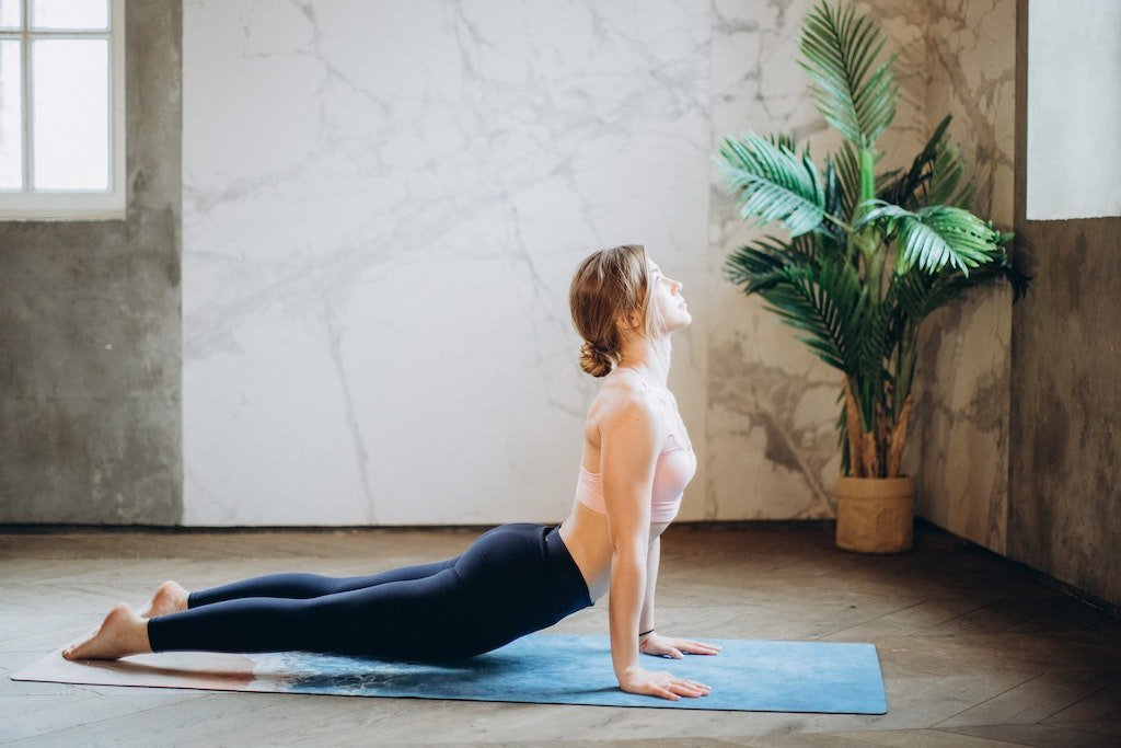Healthy woman holding yoga pose on mat.