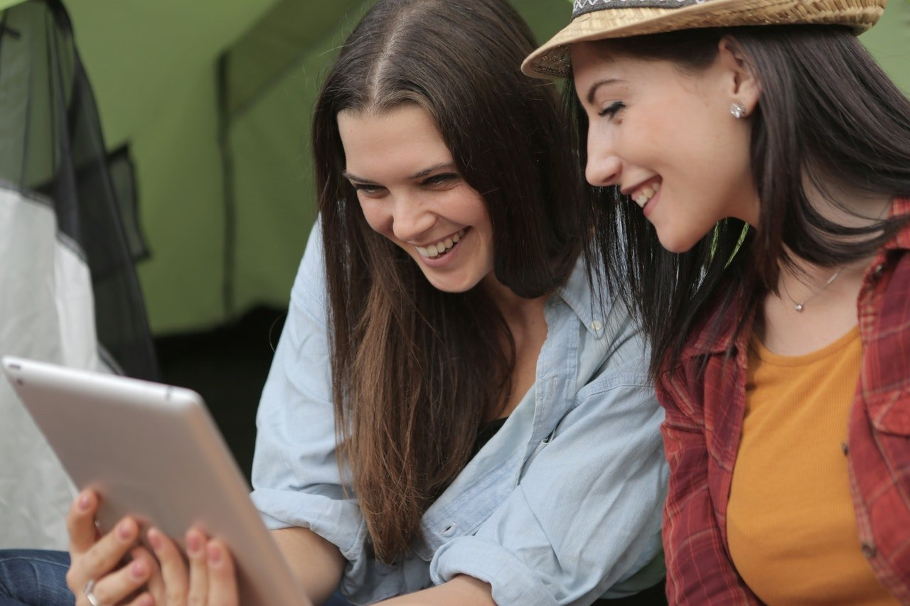 Two young women holding iPad. Weight loss success.