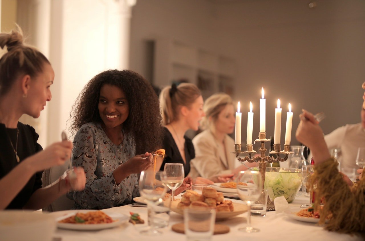 Women eating pasta at table.