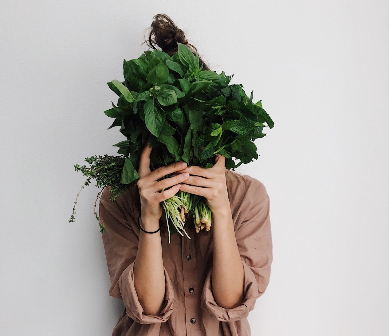 Young woman holding green plants over her face; Paleo diet