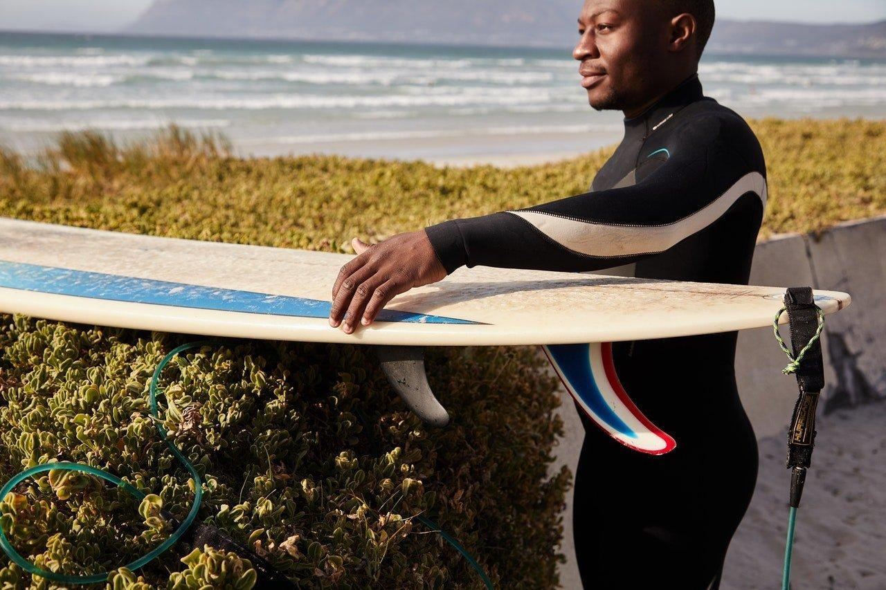 Healthy man surfing at beach.
