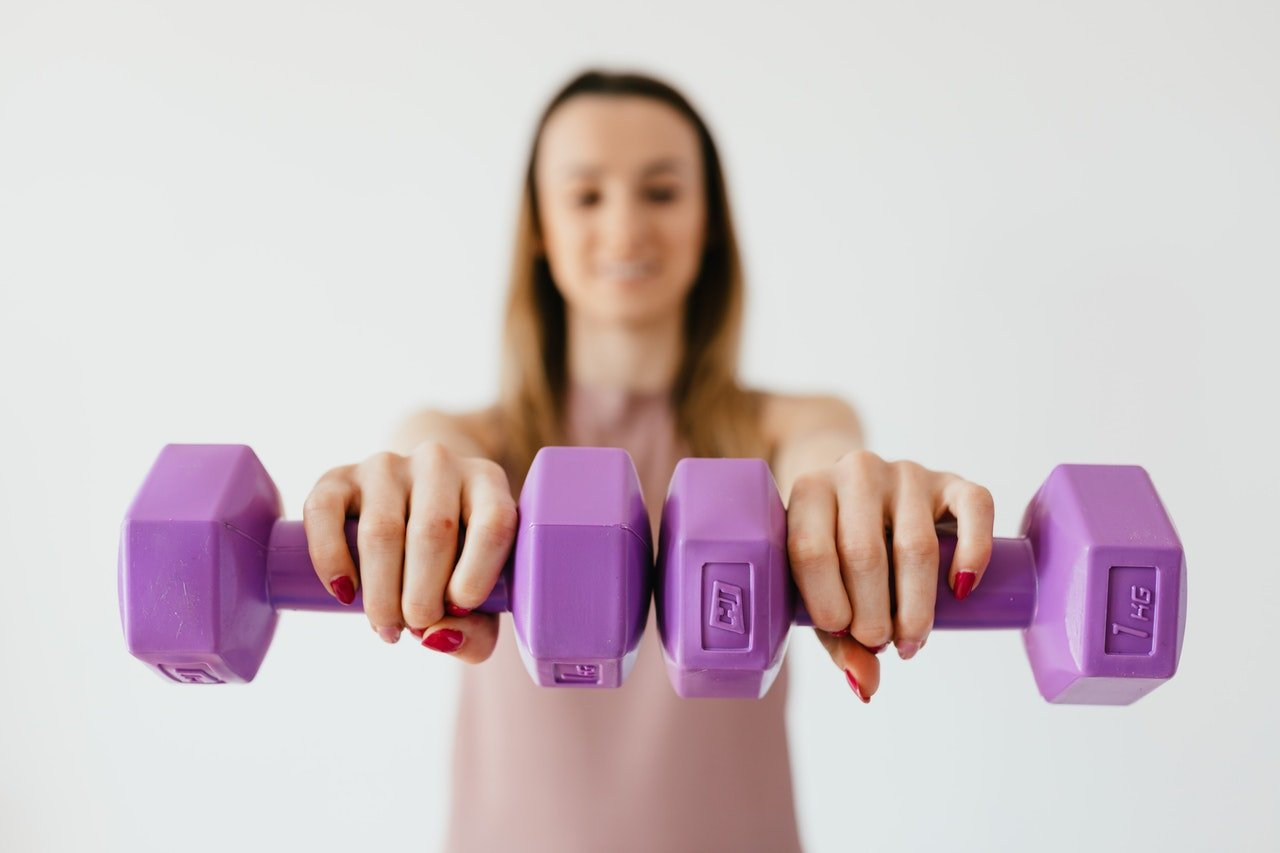 Woman holding hand weights.