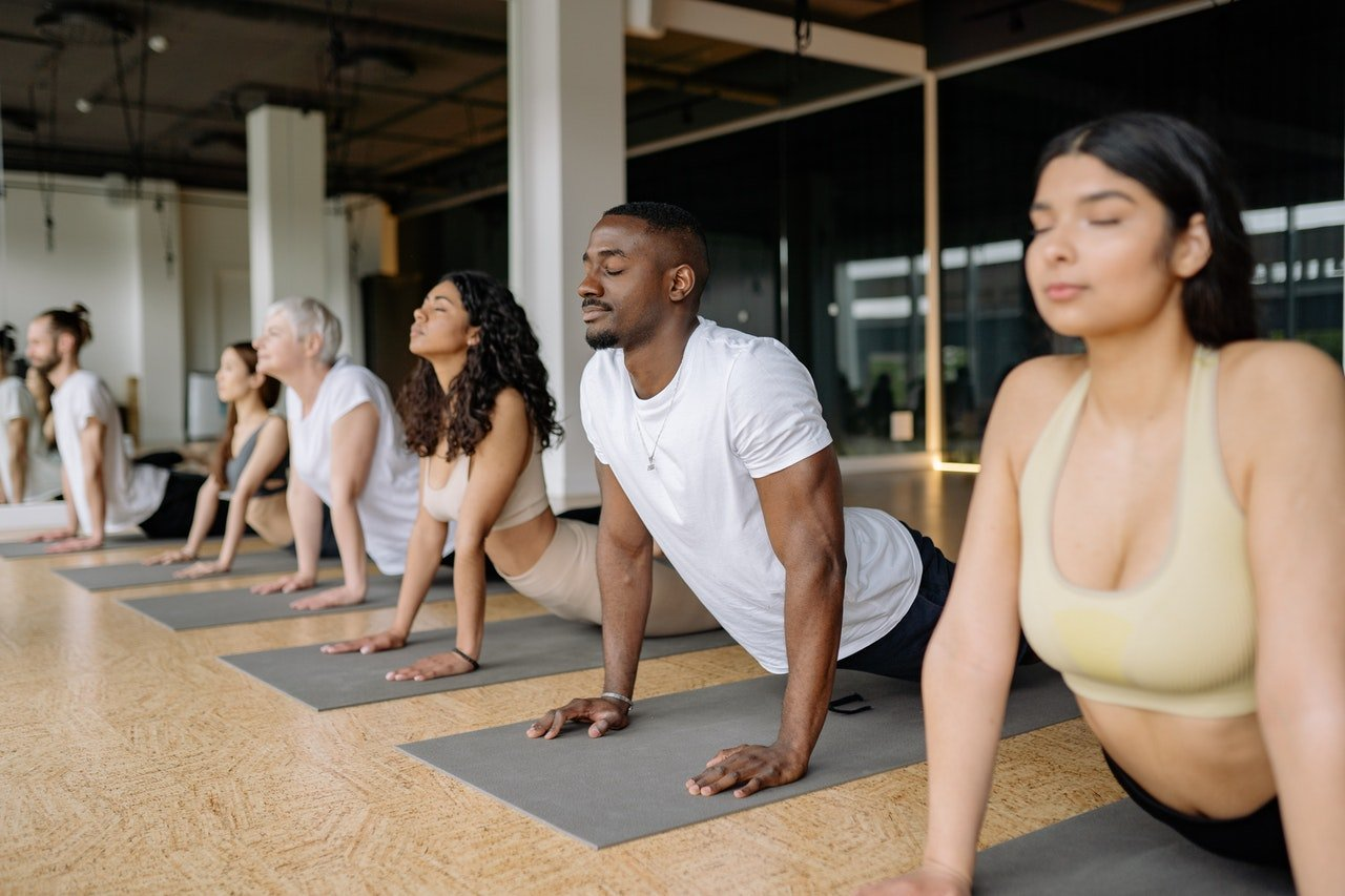Women and men holding yoga pose side by side.