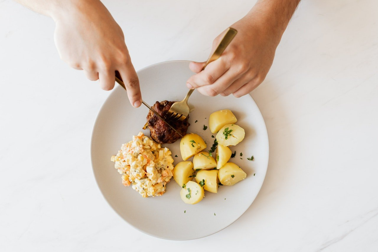 Person holding fork and knife over plate of carbs.